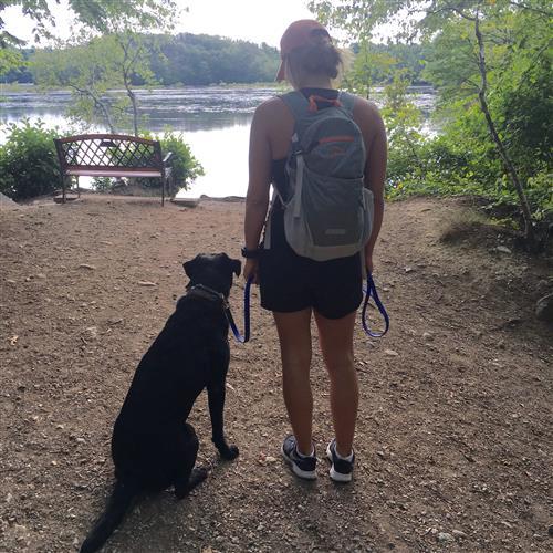 Hiker and dog looking at a lake